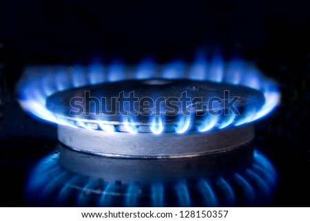 Fire and its reflection on gas-top range - stock photo