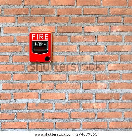 fire break glass alarm switch on brick wall background - stock photo