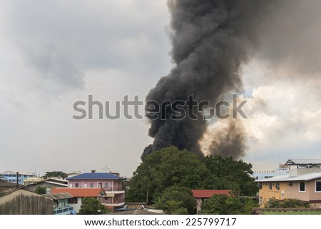 Fire burning and black smoke over rubber factory behind the big tree. - stock photo