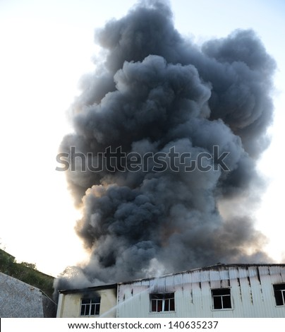 Fire burning and black smoke over the house. - stock photo
