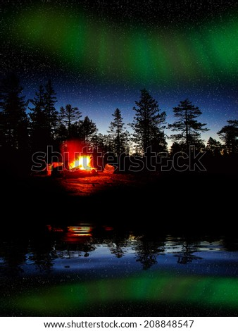 Fire burning at night in a forest with northern lights - stock photo