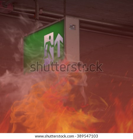 Fire burning with emergency exit sign in building - stock photo