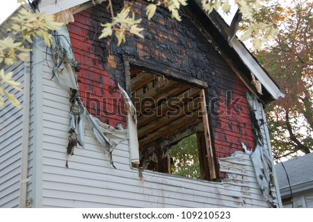 fire damaged home with melted siding and broken glassfire damaged home with melted siding and broken glass - stock photo