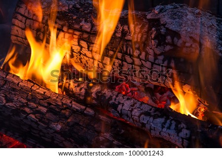 Fire dances on burning, charred logs  with red embers beneath. - stock photo
