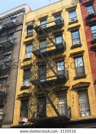 Fire escapes run diagonally down colorful apartment buildings in Greenwich Village, NYC. - stock photo