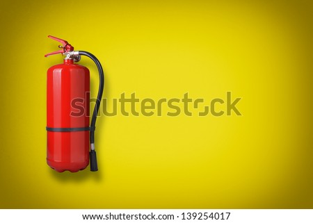 Fire extinguisher on the yellow wall - stock photo