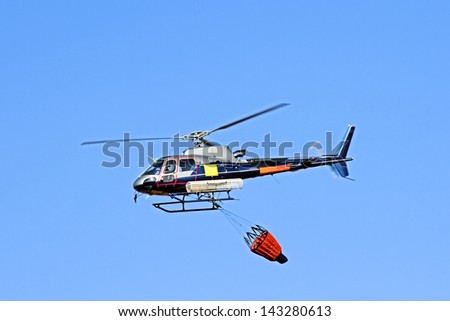 Fire fighter helicopter with a water bag - stock photo