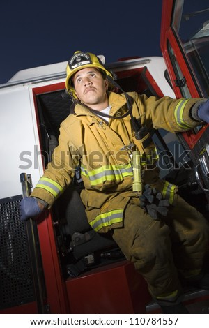Fire fighter standing at fire truck's door - stock photo