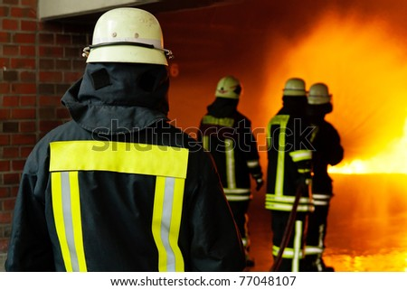 Fire-fighters in action training fire extinguish techniques - stock photo