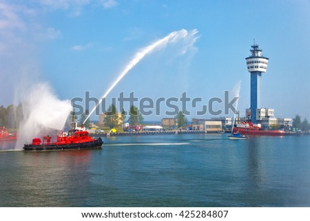 Fire fighting boat sprays water in port. - stock photo