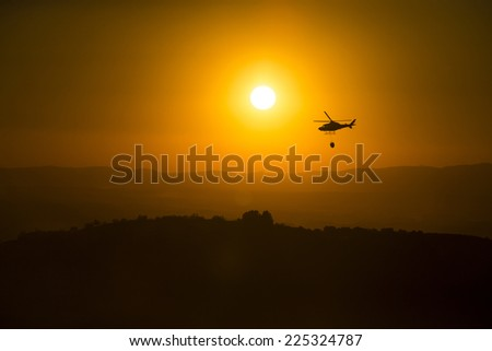 Fire fighting helicopter over burning forest at sunset. - stock photo