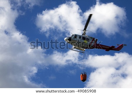 Fire fighting helicopter with waterbag on his way to combat the forest fire - stock photo