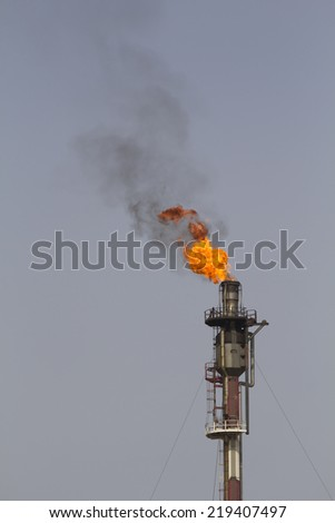 Fire from a gas torch, in a large oil refinery - stock photo