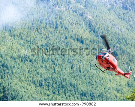 Fire Helicopter fighting a forest fire on a hot sunny day, with pilot watch below as he fills his water bag. - stock photo