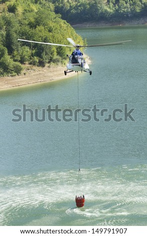 Fire helicopter filling with water  - stock photo