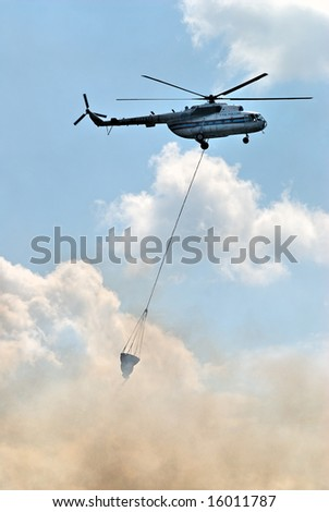 Fire helicopter in action over burning forest - stock photo