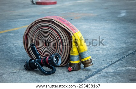 Fire-hose and nozzle on the rough ground - stock photo