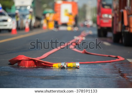 fire hose lay down on the road while the operating of fireman  - stock photo