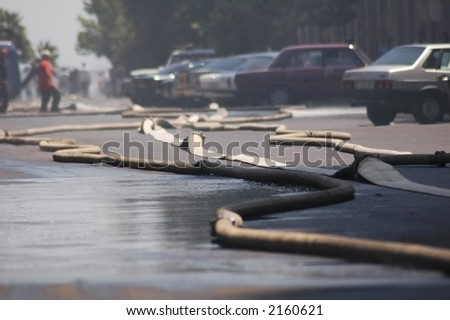 Fire hoses stretching across the street during fire in the city - stock photo