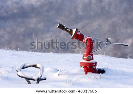 Fire hydrant in the snowy helipad, Italy (also known colloquially as fire plug in the United States or as johnny pump in New York City). - stock photo