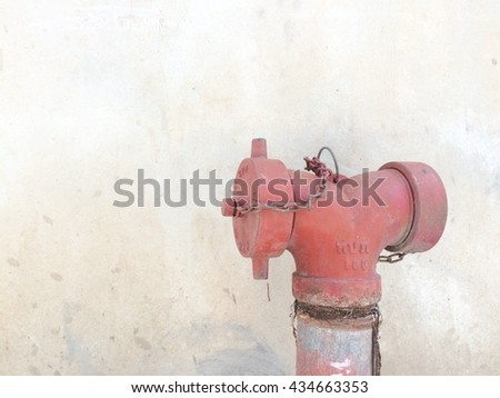 Fire hydrant on front of concrete wall texture background - stock photo