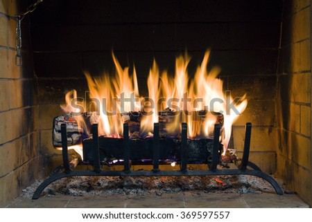Fire in fireplace. Closeup of firewood burning in fire. Fireplace in the house. Firewood burns in a fireplace. A fireplace in a country house - stock photo