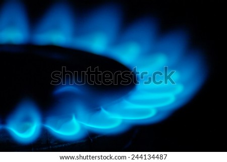 Fire natural gas burner in home on a dark background - stock photo