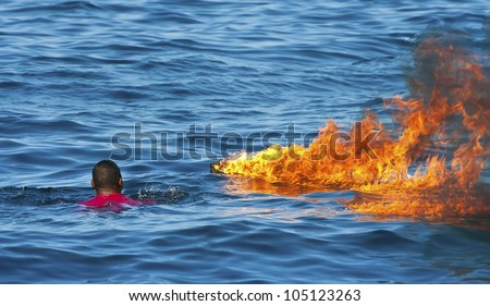 Fire on water with rescuing man - stock photo