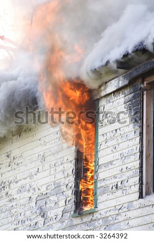 Fire pouring from a window of a house - stock photo