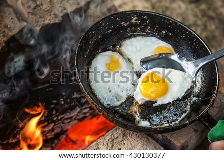 fire-roasted eggs in a frying pan and an iron shovel - stock photo