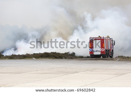 Fire truck is surrounded by smoke and fire. - stock photo