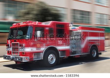 Fire truck rushing down street - stock photo