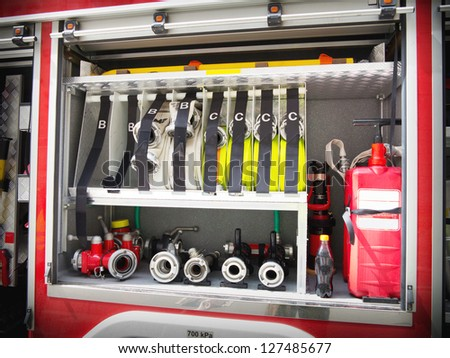 Fire valves and hoses on the side of a fire engine - stock photo