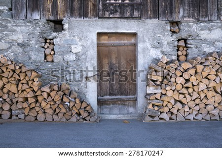 Fire Wood Stacked Outside Rustic Rural Barn with Closed Wooden Door - stock photo