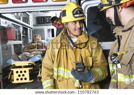 Fire workers looking at each other with patient and EMT doctor in the background - stock photo