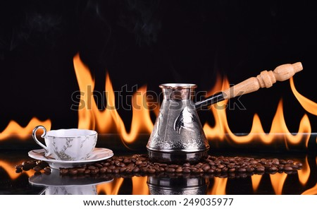 Fired cup of coffee with coffee beans and turk on dark background - stock photo