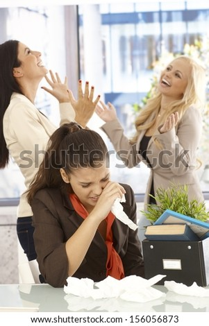 Fired female employee crying at desk, colleagues celebrating at the background. - stock photo
