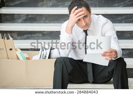 Fired frustrated man in suit sitting at stairs in office. - stock photo