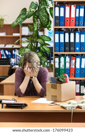 Fired woman crying, last time sitting at your desk - stock photo