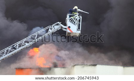 Firefighter and burning factory. - stock photo
