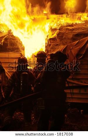 Firefighter battles house fire - stock photo