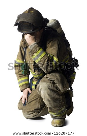 Firefighter crouching and sad - stock photo