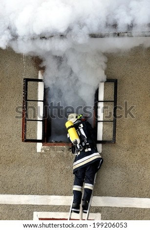 Firefighter fighting for a fire attack on the side of a house - stock photo