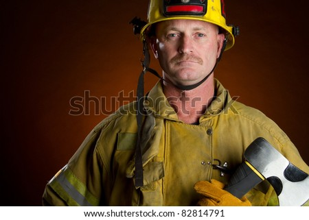 Firefighter fireman man holding axe - stock photo