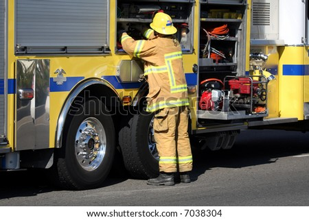 Firefighter getting gear from the fire truck - stock photo
