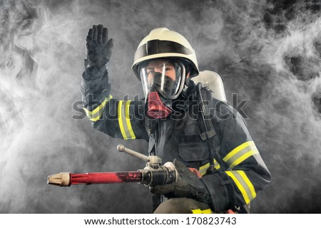 Firefighter giving directions in burning place - stock photo