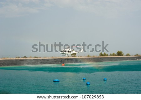 Firefighter helicopter loading water while extiguishing a forest fire - stock photo