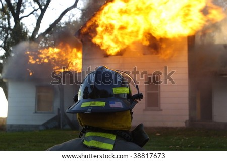 firefighter in foreground of fire - stock photo