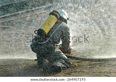 Firefighter in protective suit works with water cannon - stock photo