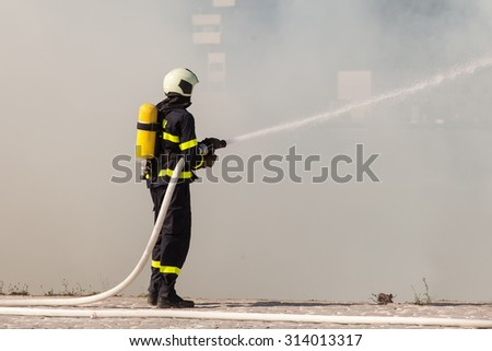 Firefighter in protective suit works with water hose. Fighting for a fire attack - stock photo